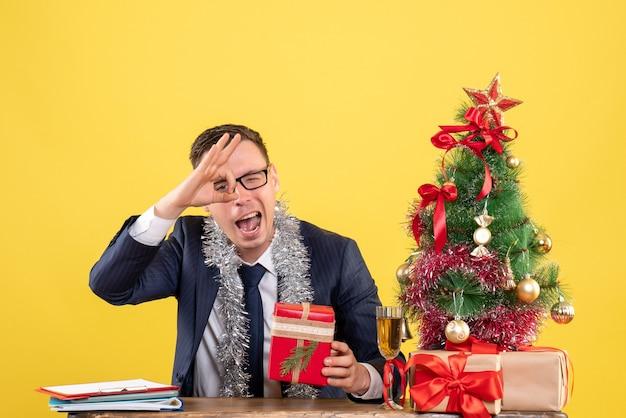 Junger mann, der ok zeichen vor auge macht, das am tisch nahe weihnachtsbaum sitzt und auf gelb präsentiert