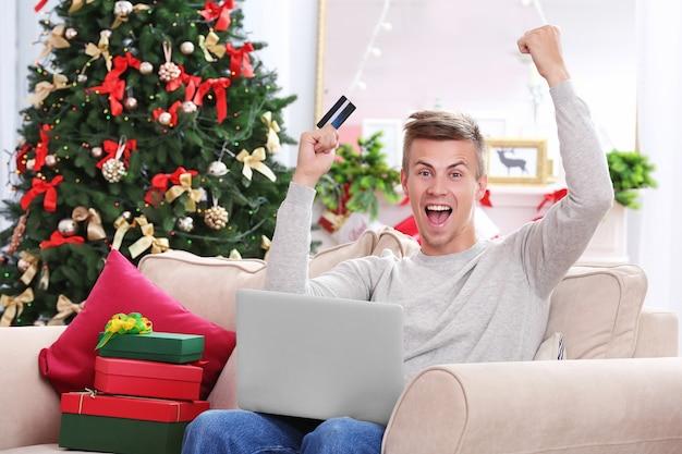Junger mann, der online mit kreditkarte zu hause für weihnachten einkauft