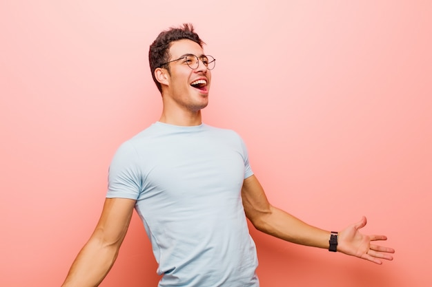 Junger mann, der oper durchführt, romantisch, künstlerisch und leidenschaftlich über rosa wand fühlt