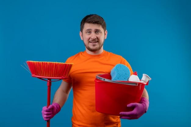 Junger mann, der orange t-shirt hält eimer mit reinigungswerkzeugen und mopp lächelnd betrachtet kamera positiv und glücklich bereit zu reinigen steht über blauem hintergrund