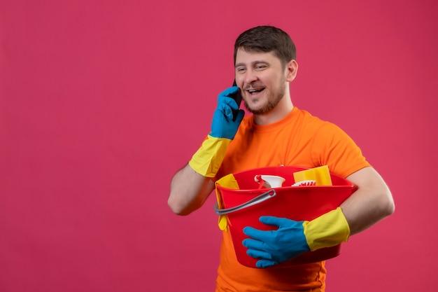 Junger mann, der orange t-shirt und gummihandschuhe hält eimer mit reinigungswerkzeugen hält