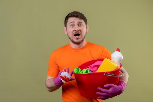 Junger mann, der orange t-shirt und gummihandschuhe hält eimer mit reinigungswerkzeugen und schrubbbürste hält