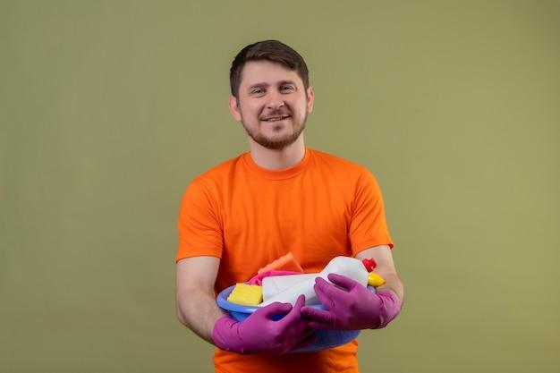 Junger mann, der orange t-shirt und gummihandschuhe trägt, die becken mit reinigungswerkzeugen halten