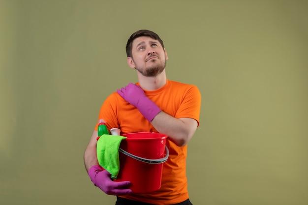 Junger mann, der orange t-shirt und gummihandschuhe trägt, die eimer mit reinigungswerkzeugen halten, die müde und überarbeitete berührende schulter sehen, die schmerz haben, der über grüner wand steht