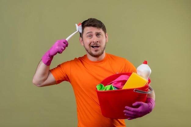 Junger mann, der orange t-shirt und gummihandschuhe trägt, die eimer mit reinigungswerkzeugen halten, die seinen kopf mit der bürste kratzen
