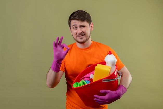 Junger mann, der orange t-shirt und gummihandschuhe trägt, die eimer mit reinigungswerkzeugen halten, die zuversichtlich lächelnd positiv und glücklich tun, ok zeichen zu stehen, das über grüner wand 2 steht