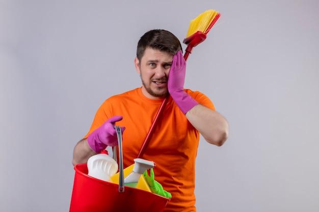 Junger mann, der orange t-shirt und gummihandschuhe trägt, die eimer mit reinigungswerkzeugen halten, und mopp verwirrte, berührenden kopf für fehler, der über grüner wand steht