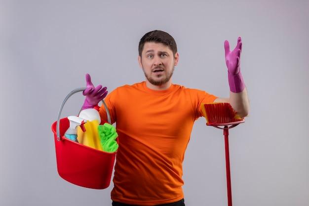 Junger mann, der orange t-shirt und gummihandschuhe trägt, die eimer mit reinigungswerkzeugen und mopp halten, missfallen mit verwirrtem ausdruck auf gesicht, das über weißer wand steht