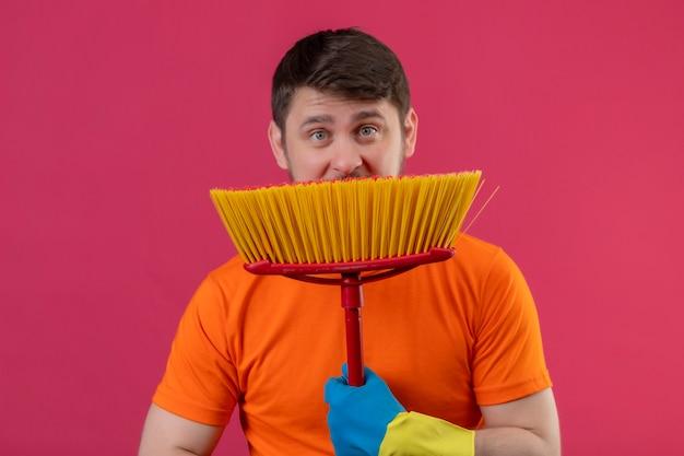Junger mann, der orange t-shirt und gummihandschuhe trägt, die mopp halten, der sich dahinter versteckt, überrascht, über rosa wand zu stehen