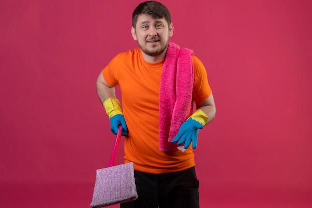 Junger mann, der orange t-shirt und gummihandschuhe trägt, die mopp mit erhobenem arm halten, als eine frage stellen, die über rosa wand steht