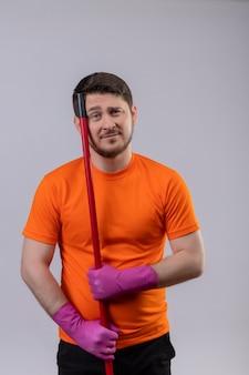 Junger mann, der orange t-shirt und gummihandschuhe trägt, die mopp mit traurigem ausdruck auf gesicht halten, das über weißer wand steht