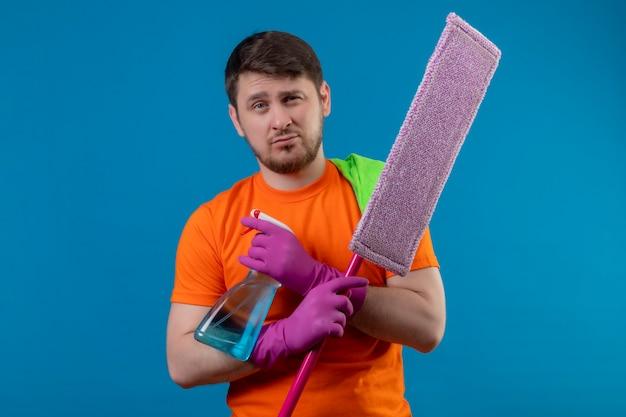 Junger mann, der orange t-shirt und gummihandschuhe trägt, die mopp und reinigungsspray mit skeptischem ausdruck halten