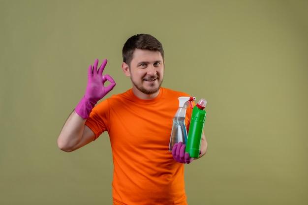 Junger mann, der orange t-shirt und gummihandschuhe trägt, die reinigungsmittel halten, die glücklich und positiv lächelnd ok zeichen stehen über grüner wand