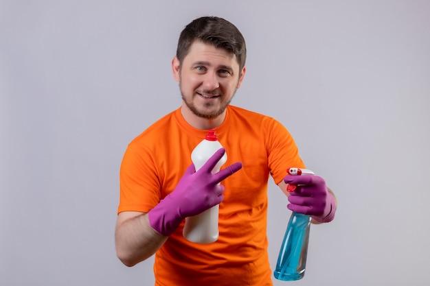 Junger mann, der orange t-shirt und gummihandschuhe trägt, die reinigungsmittel halten, die nummer zwei zeigen