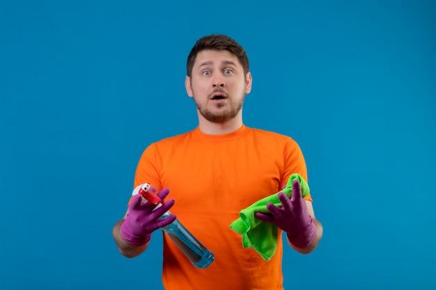 Junger mann, der orange t-shirt und gummihandschuhe trägt, die reinigungsspray und teppich halten