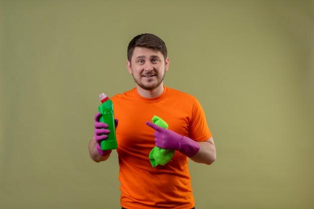 Junger mann, der orange t-shirt und gummihandschuhe trägt, die reinigungsspray und teppich zeigen, der mit finger zur flasche mit spray zeigt, der fröhlich positiv und glücklich betrachtet kamera auf grünem hintergrund lächelt