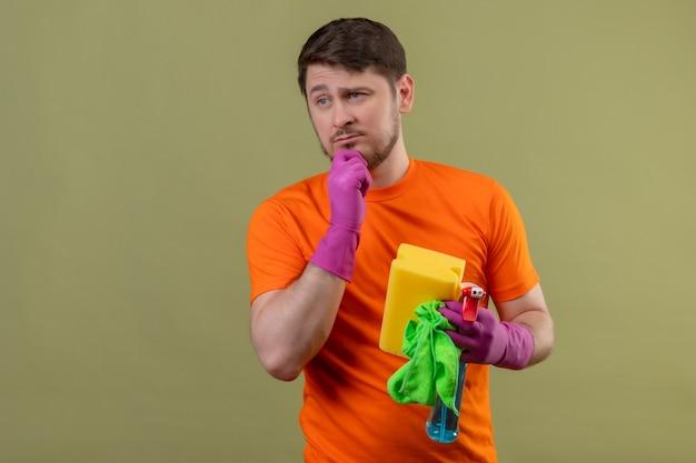 Junger mann, der orange t-shirt und gummihandschuhe trägt, die reinigungswerkzeuge halten, die mit nachdenklichem ausdruck auf gesicht denken, das über grüner wand steht