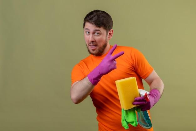Junger mann, der orange t-shirt und gummihandschuhe trägt, die reinigungswerkzeuge souverän und glücklich halten, nummer zwei oder siegeszeichen zeigend über grüner wand zeigend
