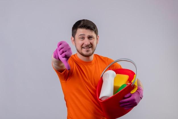 Junger mann, der orange t-shirt und gummihandschuhe trägt eimer mit reinigungswerkzeugen lächelnd zeigt daumen nach unten stehend über weiße wand