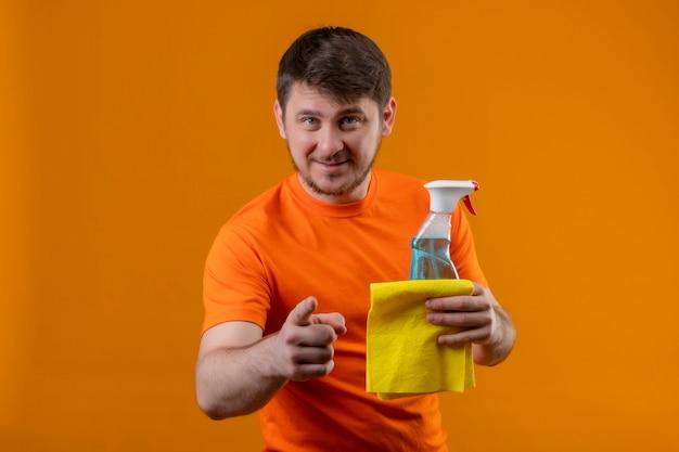 Junger mann, der orange t-shirt und gummihandschuhe trägt, zeigt auf kamera mit finger, der reinigungsspray und teppich hält