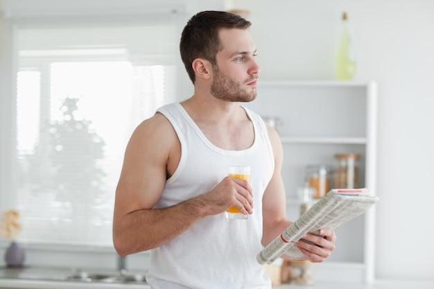 Junger mann, der orangensaft beim lesen der nachrichten trinkt