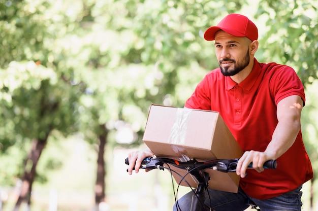 Junger mann, der paket auf einem fahrrad liefert