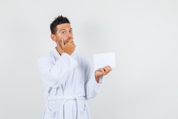 Junger mann, der papierblatt mit hand auf mund im weißen bademantel hält und überrascht, vorderansicht schaut.