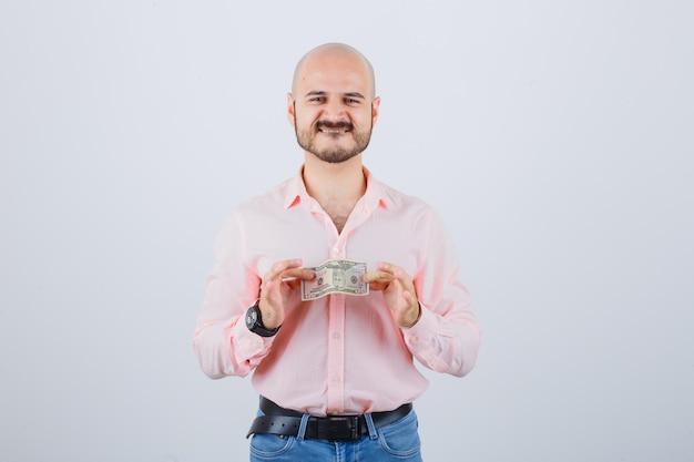 Junger mann, der papiergeld in rosa hemd, jeans hält und zufrieden aussieht, vorderansicht.