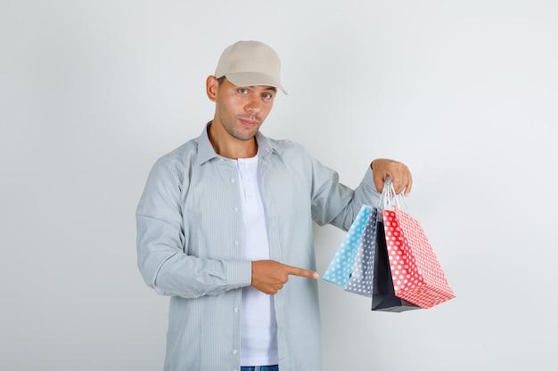 Junger mann, der papiertüten im hemd mit kappe, jeans zeigt