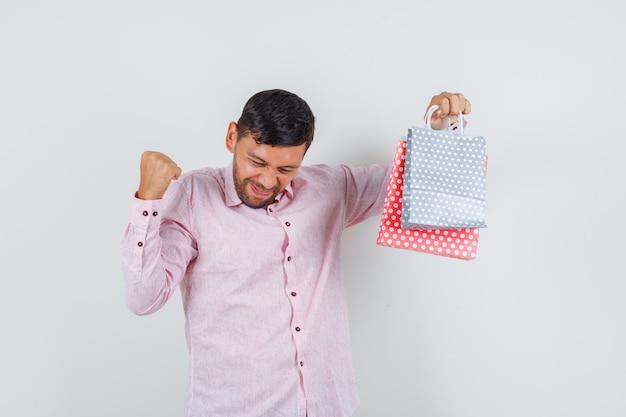 Junger mann, der papiertüten mit siegergeste im hemd hält und glückliche vorderansicht schaut.