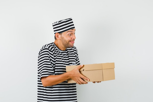 Junger mann, der pappkarton im gestreiften t-shirt, hut präsentiert und sanft schaut.