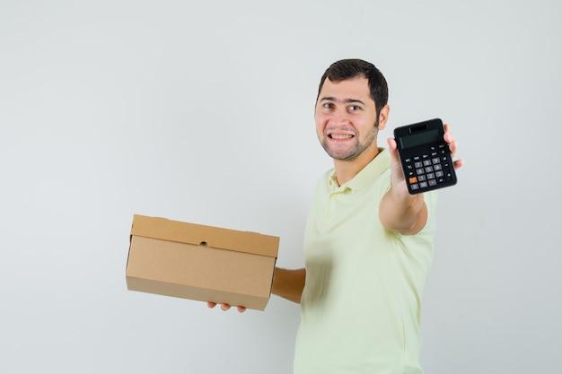Junger mann, der pappkarton und taschenrechner im t-shirt hält und fröhlich schaut. vorderansicht.