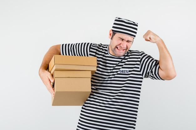 Junger mann, der pappkartons im t-shirt, im hut hält und glück schaut. vorderansicht.