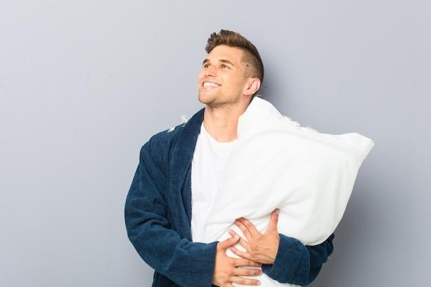 Junger mann, der pijama hält, der ein kissen hält, das zuversichtlich mit verschränkten armen lächelt.