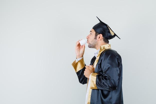 Junger mann, der pillen in graduierter uniform nimmt.
