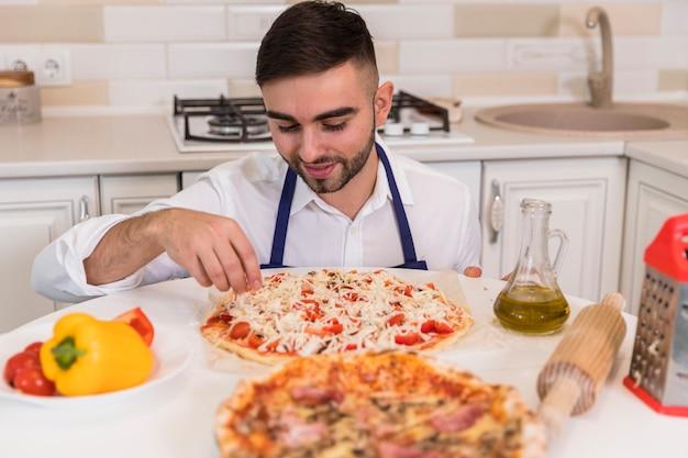Junger mann, der pizza in der küche kocht