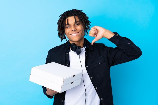Junger mann, der pizzakästen über lokalisierter wand hält