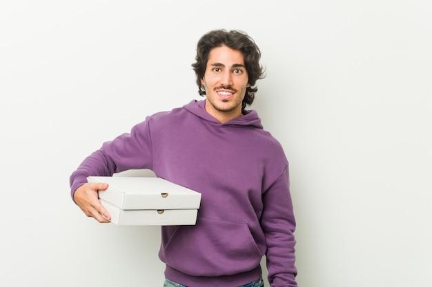 Junger mann, der pizzapaket glücklich, lächelnd und nett hält.