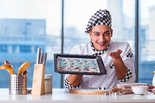 Junger mann, der plätzchen in der küche kocht
