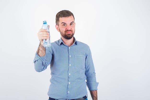 Junger mann, der plastikwasserflasche im hemd, in den jeans zeigt und zuversichtlich schaut. vorderansicht.