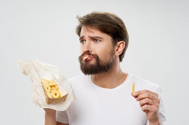 Junger mann, der pommes frites isst