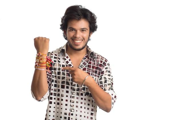 Junger mann, der rakhi auf seiner hand anlässlich des raksha bandhan festivals zeigt.