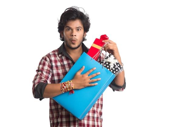 Junger mann, der rakhi auf seiner hand mit einkaufstüten und geschenkbox anlässlich des raksha bandhan festivals zeigt.