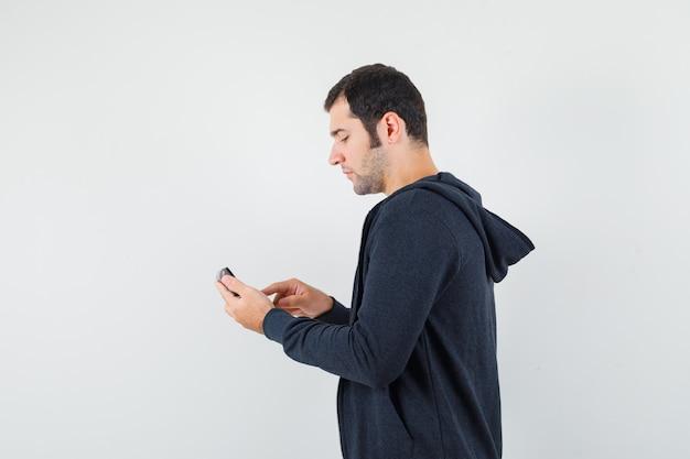 Junger mann, der rechner hält und einige operationen auf ihm im weißen t-shirt und im schwarzen kapuzenpullover mit reißverschluss vorne ausführt und fokussierte vorderansicht sieht.