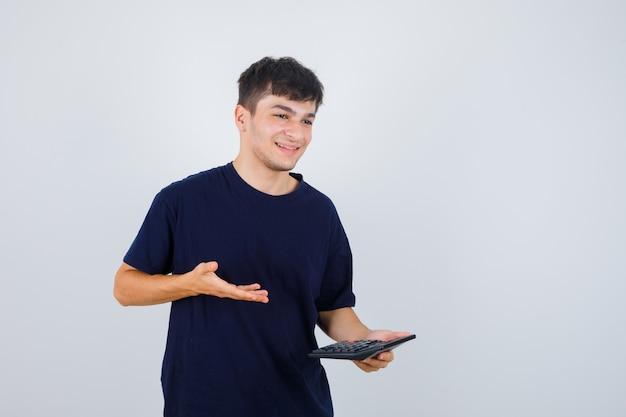 Junger mann, der rechner im schwarzen t-shirt hält und fröhlich schaut. vorderansicht.