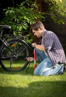 Junger mann, der reifen auf seinem fahrrad im park aufpumpt