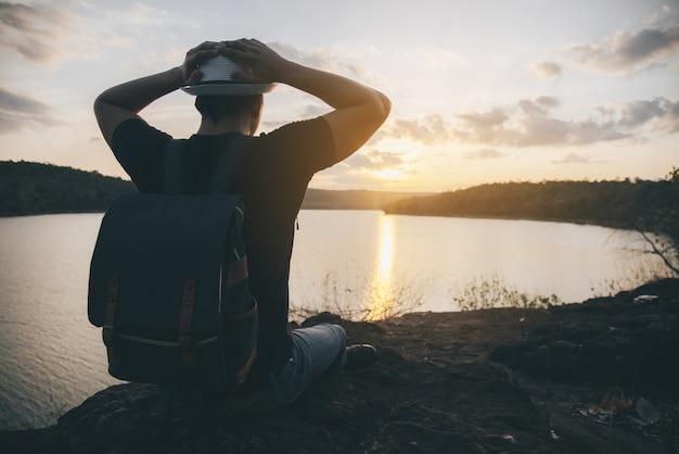 Junger mann der reise bei sonnenuntergang