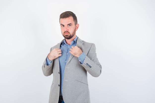 Junger mann, der revers hält, während er in hemd, jeans, anzugjacke aufwirft und ernsthafte vorderansicht sieht.