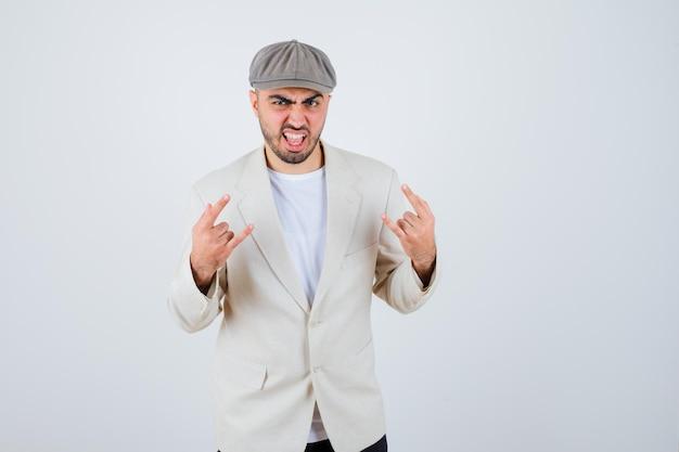 Junger mann, der rock n roll-schild zeigt, in weißem t-shirt, jacke und grauer mütze eine grimasse verzieht und wütend aussieht