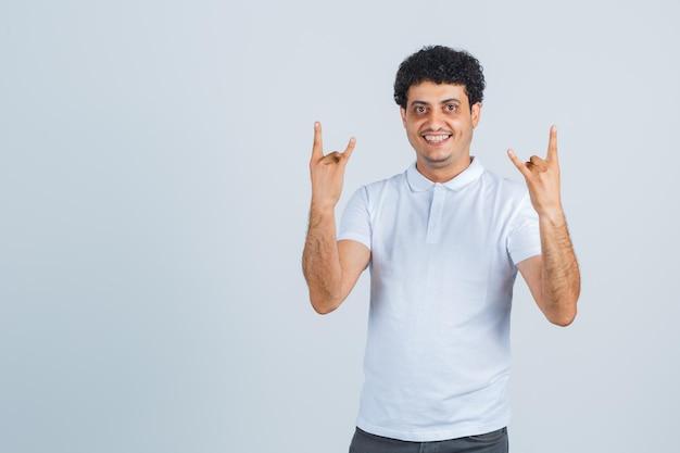 Junger mann, der rocksymbol im weißen t-shirt, in der hose tut und glückselig aussieht. vorderansicht.
